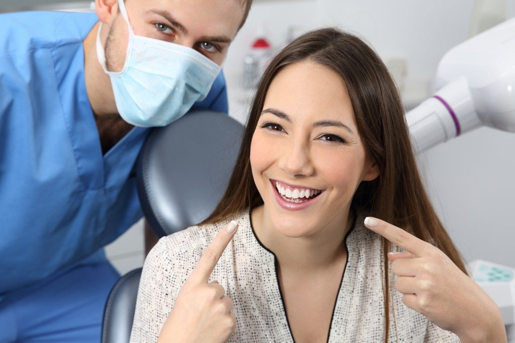 Woman whitening her teeth at dental clinic