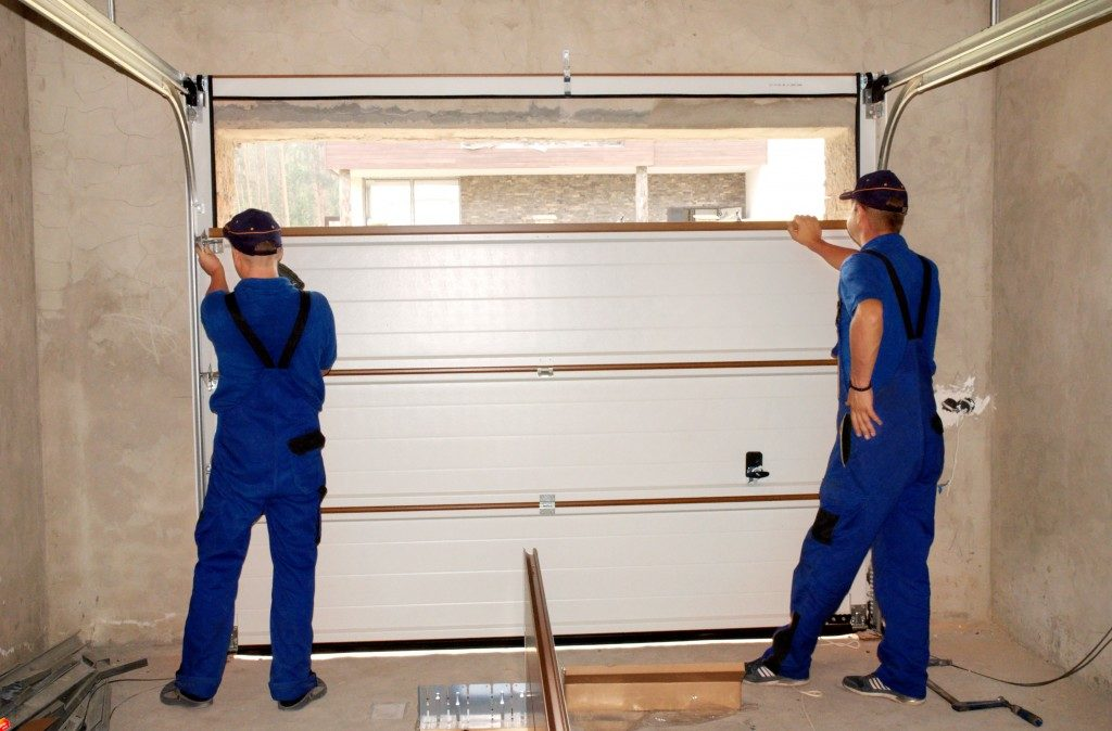 men installing a garage door