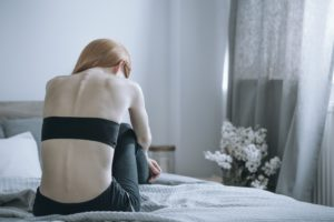 woman in bed suffering from anorexia