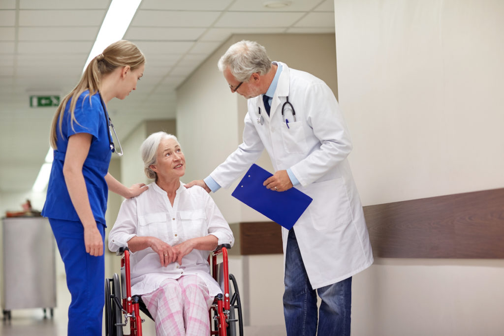 doctor and nurse talking to elderly patient