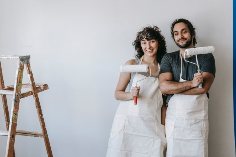 couple holding paint rollers