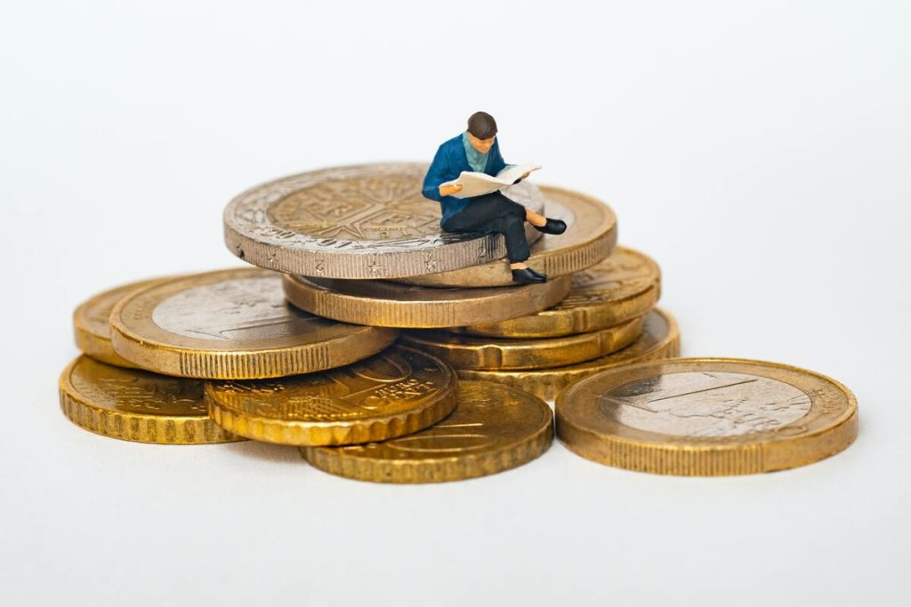man reading sitting on top of coins